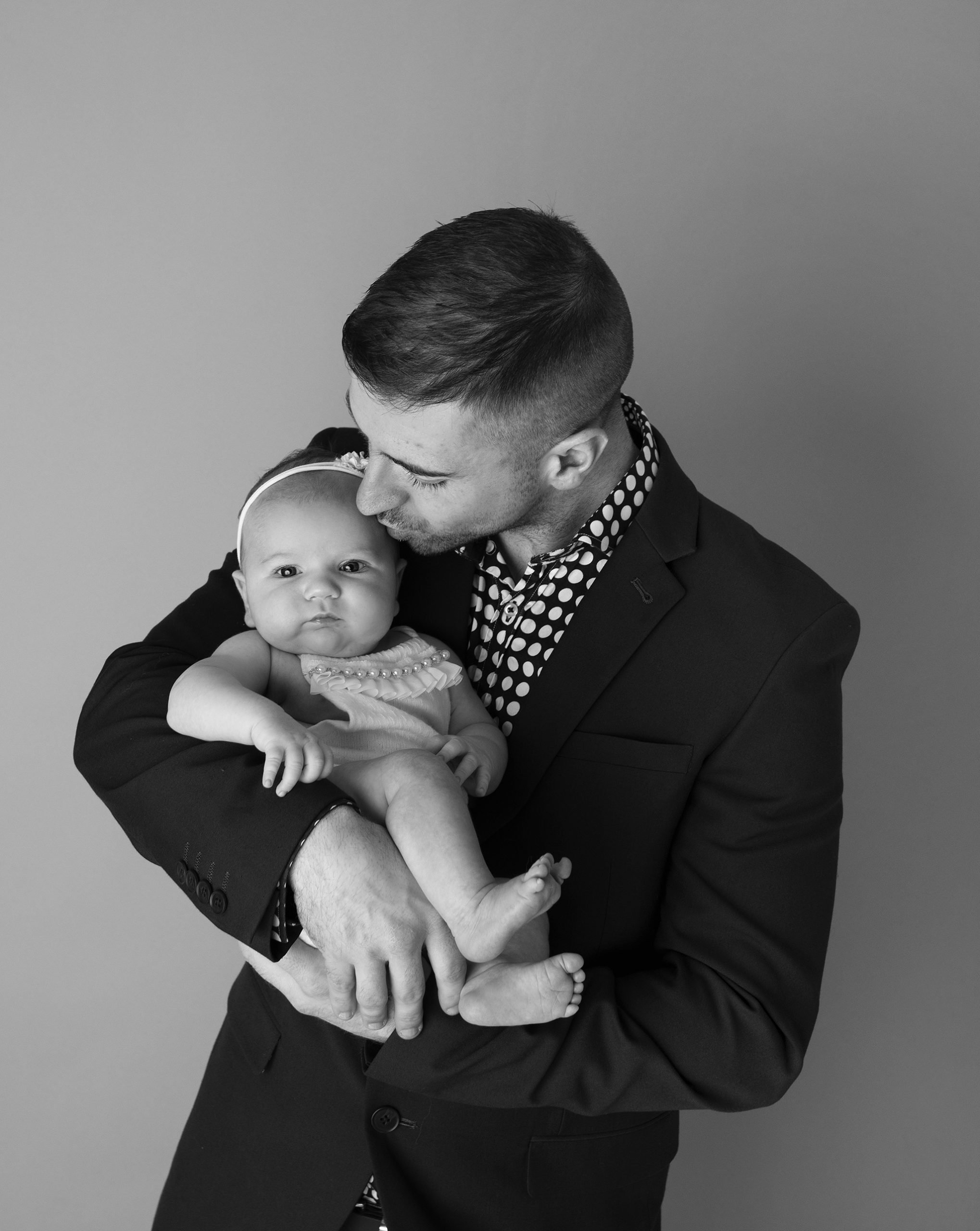 Dad kissing baby